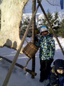 Elissa tests out a drum at the Anishinabe (Algonquin) village.