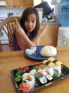 Our nine-year-old gets set to dig into her steamed meat bun and sushi.